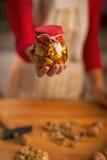 Primer en el ama de casa que sostiene el tarro con las nueces de la miel Foto de archivo libre de regalías