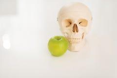 Primer en el cráneo humano y manzana en la tabla Foto de archivo