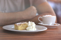 Primer en el hombre que se sienta en el café que tiene pedazo de torta dulce cremosa Fotografía de archivo