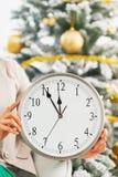 Primer en el reloj a disposición de la mujer delante del árbol de navidad Imágenes de archivo libres de regalías
