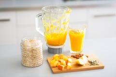 Primer en el smoothie y los ingredientes de la calabaza en la tabla Foto de archivo libre de regalías