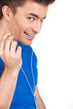 Primer en individuo sonriente en música que escucha de los auriculares en el fondo blanco Foto de archivo libre de regalías