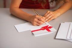 Primer en la escritura de la mujer en letra de la Navidad en cocina foto de archivo