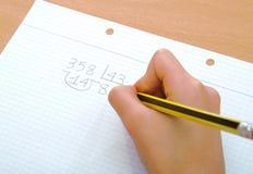 Primer en la mano de un niño que hace una matemáticas Imagen de archivo
