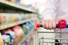 Primer en la mano del hombre o de la mujer en tienda con la carretilla o el carro de las compras en el fondo del estante del supe Imagen de archivo libre de regalías