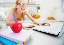 Primer en la manzana y la mujer sonriente que estudian en fondo Imágenes de archivo libres de regalías