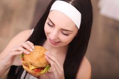 Primer en la muchacha del adolescente que come la hamburguesa Fotografía de archivo