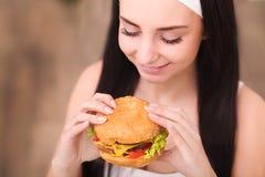 Primer en la muchacha del adolescente que come la hamburguesa Foto de archivo