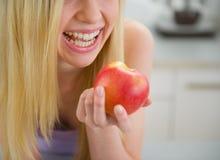 Primer en la muchacha sonriente del adolescente que come la manzana Fotografía de archivo