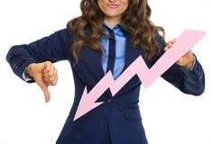 Primer en la mujer de negocios que muestra la flecha del gráfico que va abajo Fotos de archivo