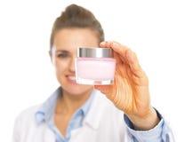 Primer en la mujer del cosmetologist que muestra la botella de nata Foto de archivo