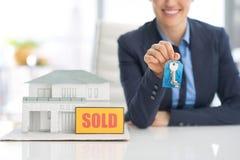 Primer en la mujer feliz del agente inmobiliario que muestra llaves fotos de archivo