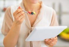 Primer en la mujer joven con PC de la tableta que come la ensalada de fruta Fotos de archivo