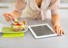 Primer en la mujer joven con PC de la tableta que come la ensalada de fruta Foto de archivo