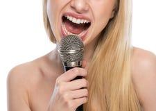 Primer en la mujer joven que canta con el micrófono Fotografía de archivo