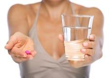 Primer en la mujer joven que da la píldora y el vidrio de agua Imágenes de archivo libres de regalías