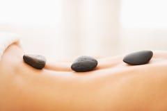 Primer en la mujer joven que recibe masaje de piedra caliente Fotos de archivo libres de regalías