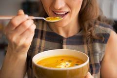 Primer en la mujer que come la sopa de la calabaza en cocina Fotografía de archivo libre de regalías