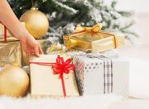 Primer en la mujer que toma la actual caja debajo del árbol de navidad Imagenes de archivo