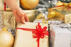 Primer en la mujer que toma la actual caja debajo del árbol de navidad Fotos de archivo libres de regalías