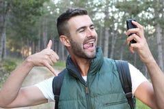 Primer en la persona que usa el teléfono elegante y mostrando el pulgar encima del finger mientras que hace una llamada video o t imagen de archivo libre de regalías