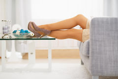 Primer en la pierna de la mujer joven que pone en el sofá Fotos de archivo