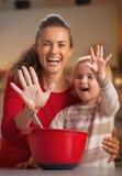 Primer en las manos de la madre y del bebé manchadas en harina Fotos de archivo libres de regalías