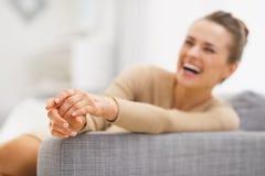 Primer en las manos de la mujer joven que se sientan en el diván fotografía de archivo