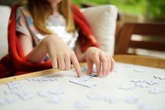 Primer en las manos del niño que montan un rompecabezas en una tabla foto de archivo