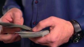 Primer en las manos que cuentan el dinero almacen de video