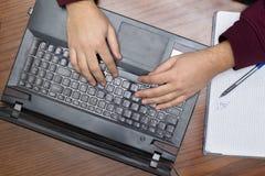 Primer en las manos que mecanografían en el teclado, el cuaderno y la pluma Fotografía de archivo