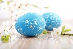 Primer en los huevos de Pascua azules con las flores en la madera Fotos de archivo libres de regalías