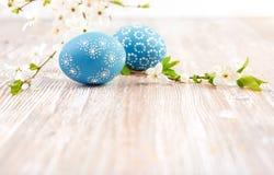 Primer en los huevos de Pascua azules con las flores en la tabla de madera, espacio Imagenes de archivo