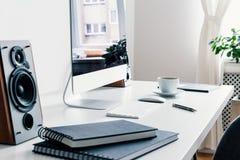 Primer en los libros, altavoz y el equipo de escritorio en el escritorio en el interior blanco del ` s del freelancer Foto verdad imagen de archivo libre de regalías