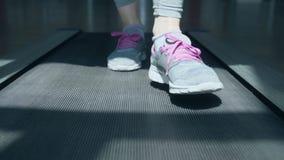 Primer en los zapatos de una mujer que corre en la rueda de ardilla en el gimnasio almacen de metraje de vídeo