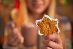 Primer en muchacha con la taza de chocolate que muestra la galleta de la Navidad Fotos de archivo libres de regalías
