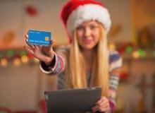 Primer en muchacha en el sombrero de santa con la PC de la tableta que muestra la tarjeta de crédito Fotos de archivo libres de regalías