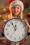 Primer en muchacha en el sombrero de santa que muestra el reloj Foto de archivo