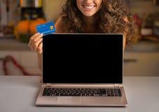 Primer en mujer con la tarjeta de crédito que muestra el ordenador portátil Imágenes de archivo libres de regalías