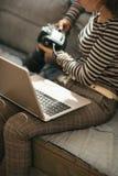 Primer en mujer joven con el ordenador portátil usando dslr Fotografía de archivo