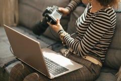Primer en mujer joven con la cámara del ordenador portátil y del dslr Fotografía de archivo