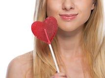 Primer en mujer joven con la piruleta en forma de corazón Imagen de archivo libre de regalías