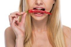 Primer en mujer joven con pimienta de chile rojo en boca Imágenes de archivo libres de regalías