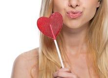 Primer en mujer joven pensativa con la piruleta en forma de corazón Fotografía de archivo libre de regalías