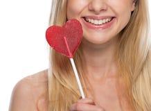 Primer en mujer joven sonriente con la piruleta en forma de corazón Imágenes de archivo libres de regalías