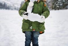 Primer en nieve en manos del niño en capa verde Fotos de archivo