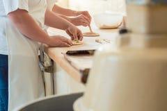 Primer en panadero en la panadería que forma el pan del pretzel fotos de archivo libres de regalías