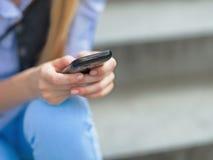 Primer en SMS de la escritura de la muchacha del inconformista mientras que se sienta en las escaleras Foto de archivo libre de regalías
