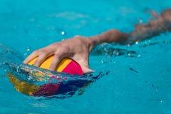 Primer en una mano que sostiene la bola del water polo durante el Griego Fotografía de archivo libre de regalías
