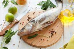 Primer de los pescados crudos en una tabla de cortar Fotografía de archivo libre de regalías